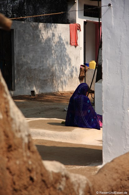 Alte Frau in einem Innenhof in Khajuraho