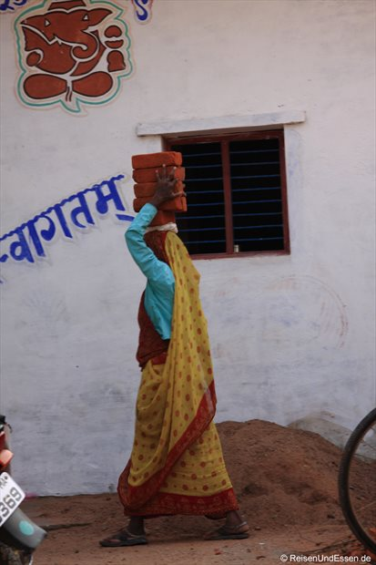 Inderin mit Ziegeln auf dem Kopf in Khajuraho