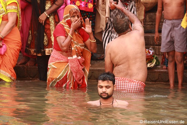 Gläubgiger Inder meditiert im heiligen Fluss Ganges