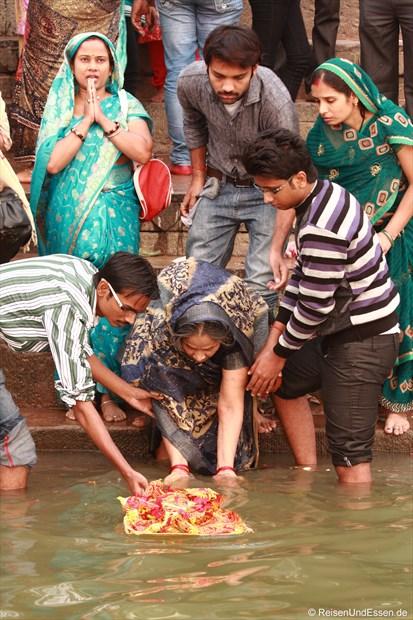 Opfergaben werden in den heiligen Fluss Ganges gesetzt