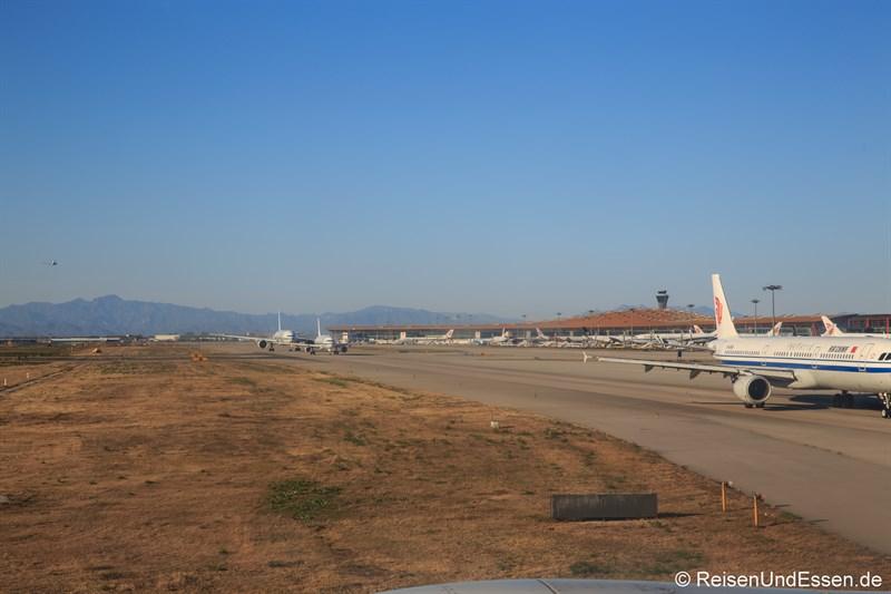 Taxiway am Beijing Capitol Airport (im Hintergrund Berge mit großer Mauer)