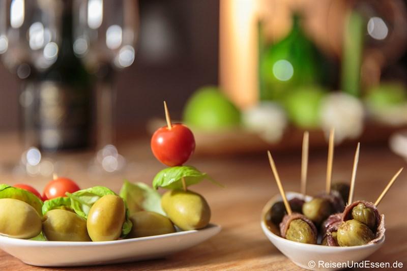 Oliven (links) und Gewürzgurken mit Sardellen