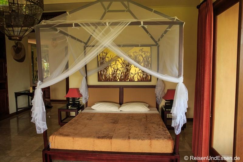 Bett mit Moskitonetz im Green Field Hotel Ubud