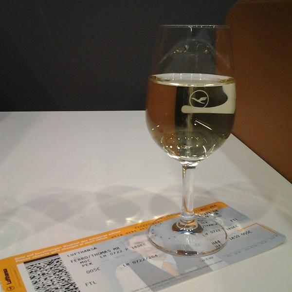 Glas Prosecco vor dem Flug mit Lufthansa von München nach Peking
