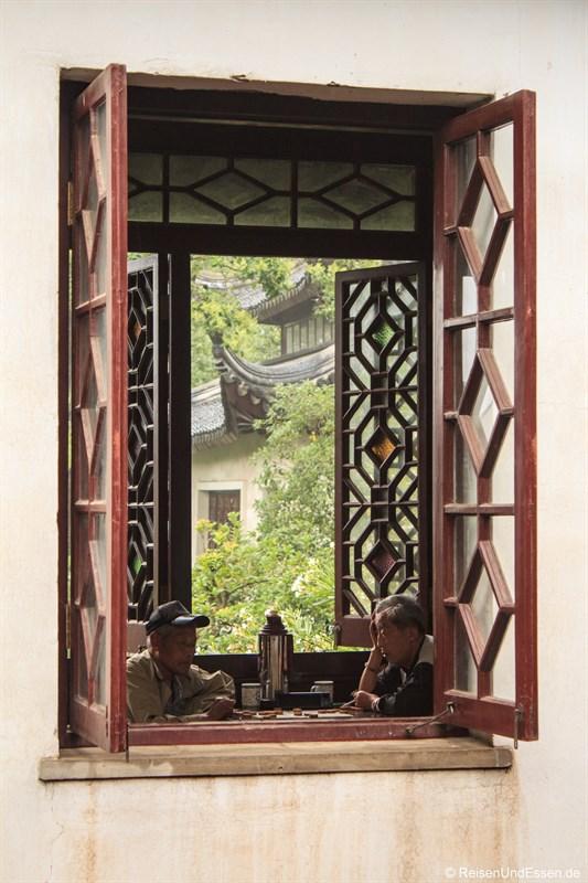 Blick in das Teehaus mit Rentner beim Schach