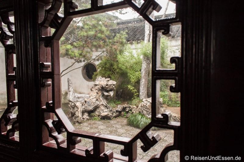 Blick durch ein Fenster auf einen Steinlöwen