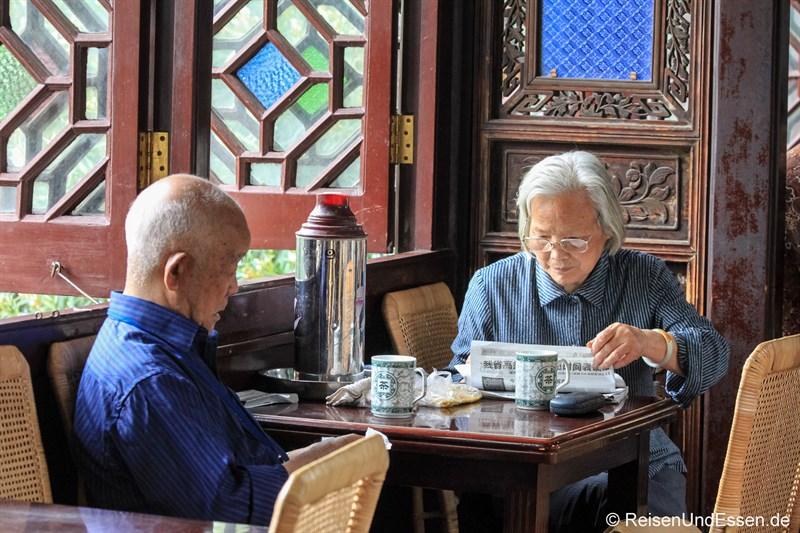 Chinesische Rentner beim Lesen und Tee