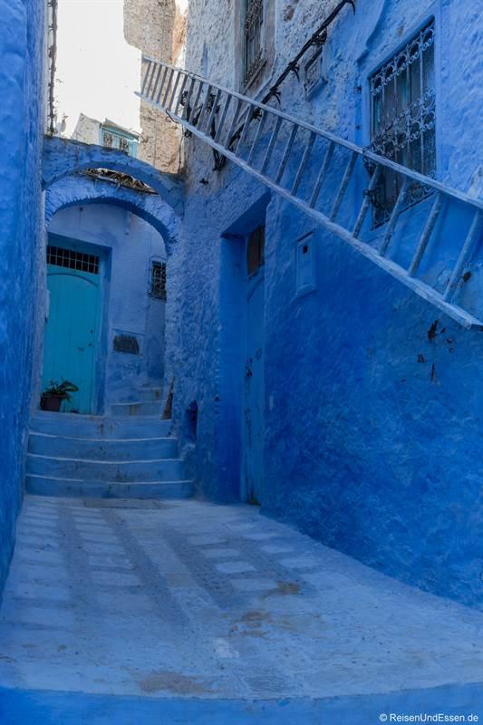 Blaue Leiter in einer Gasse