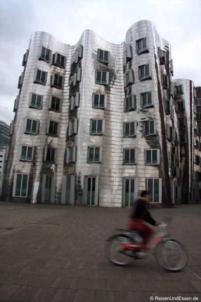 Mit dem Fahrrad an den tanzenden Häusern vorbei
