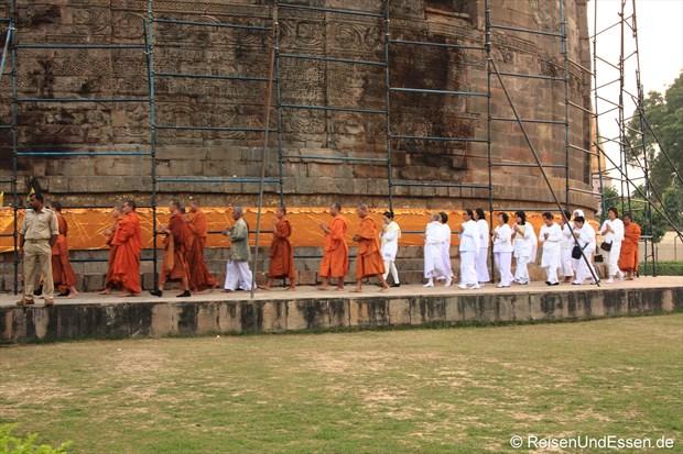Mönche umrunden in Sarnath die Dhamekh Stupa