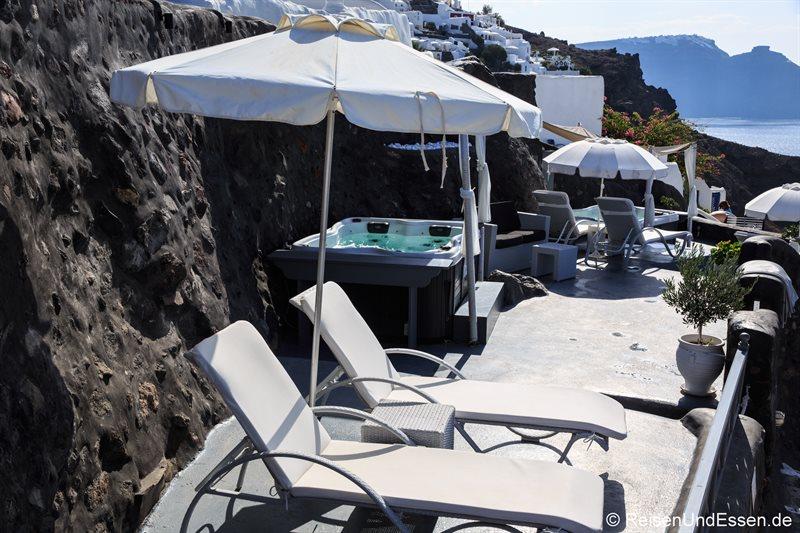 Liegestühle und Jacuzzi in einer Hotelanlage in Oia