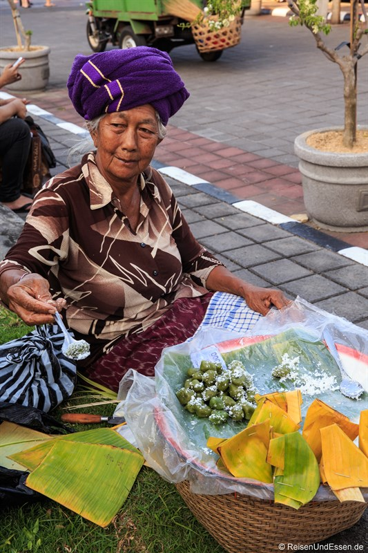Verkäuferin mit indonesischen Leckereien