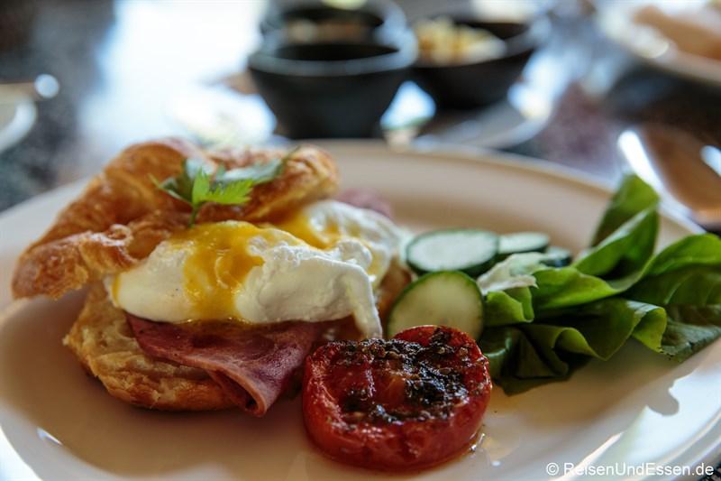 Frühstück mit Croissant, Schinken und Ei