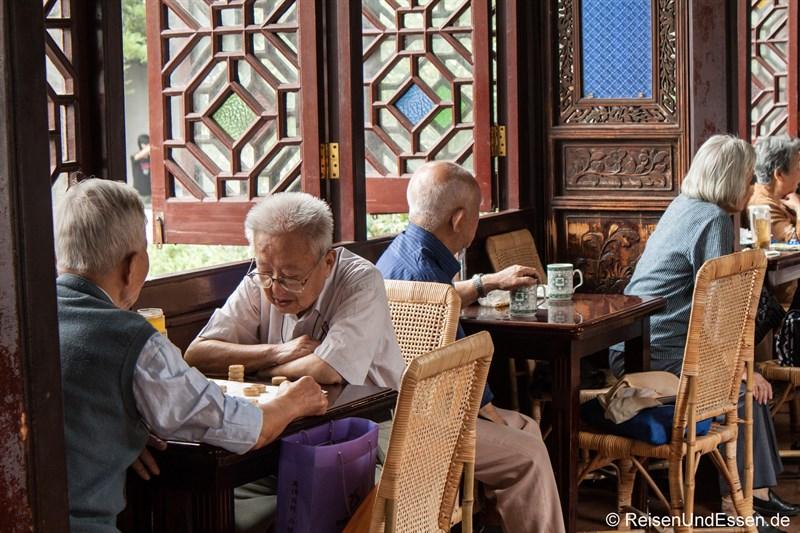 Chinesische Rentner beim Schach und Tee