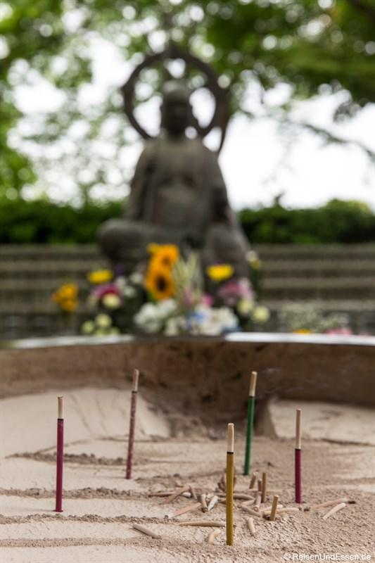 Räucherstäbchen vor einer Buddhafigur