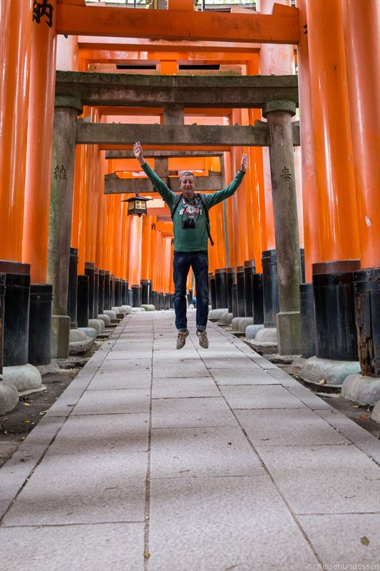 Freudensprung auf dem Weg durch die Torii