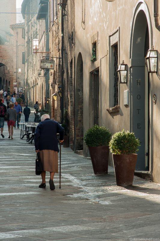 Alte Frau in einer Gasse in San Gimignano