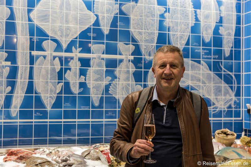 Mit Champagner vor der Fischtheke mit handbemalten Fließen im Frischeparadies München