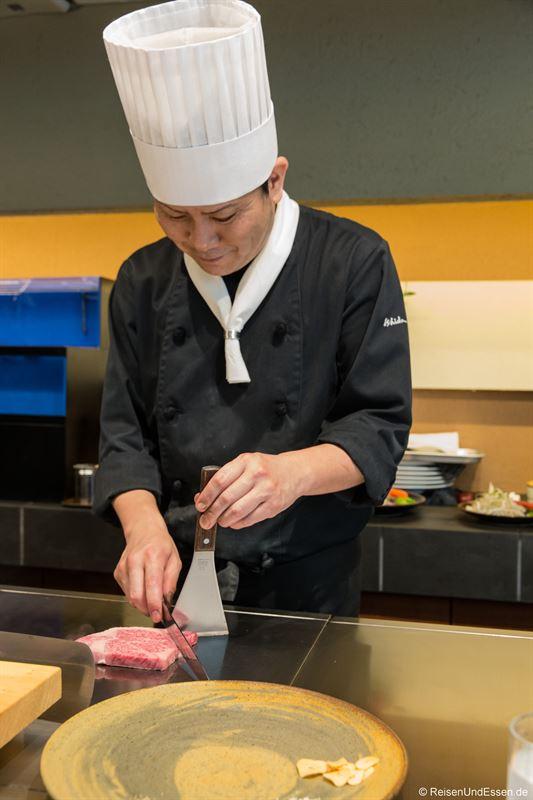 Koch bei der Zubereitung von Kobe Rind
