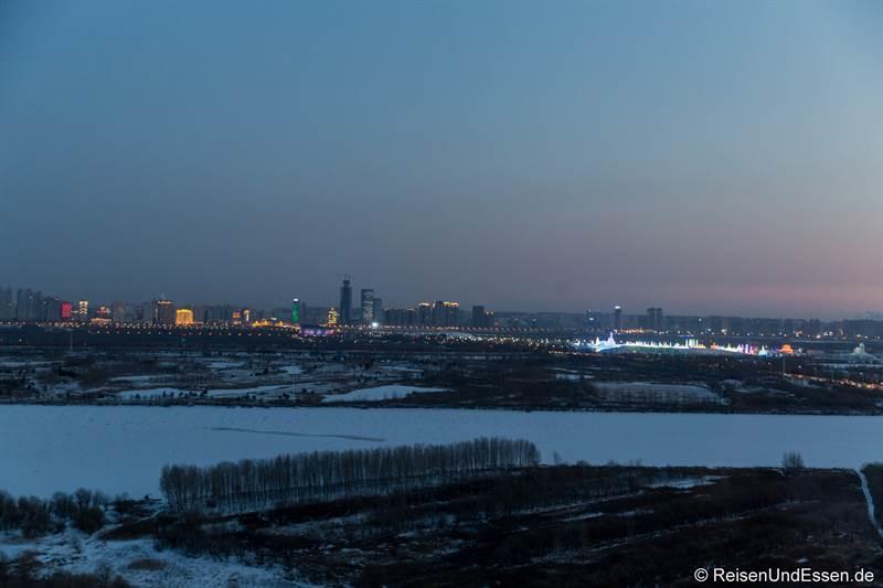 Blick auf das Schnee- und Eisfestival und die Skyline von Harbin