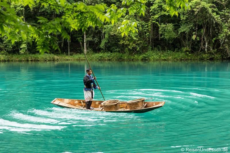 Mann im Boot auf dem Drachenteich im Nationalpark Xiaoqikong in Libo