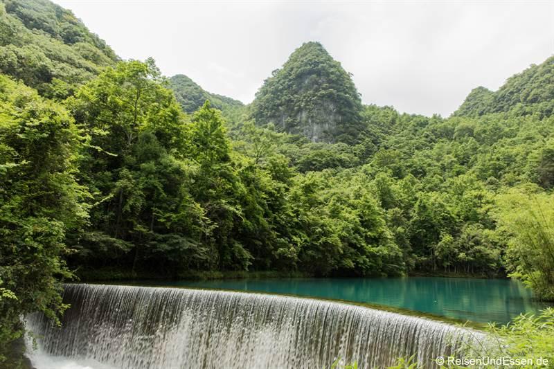Karstberge und Wasserfall beim Drachenteich im Nationalpark Xiaoqikong in Libo