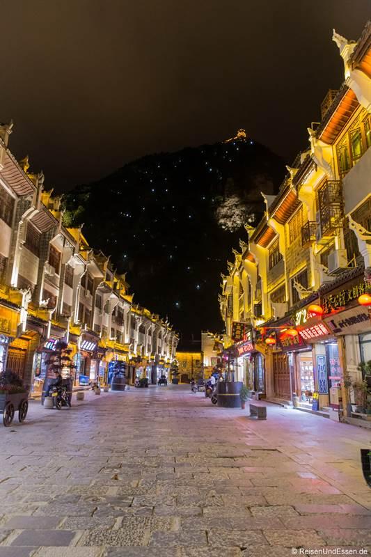 Strasse in Zhenyuan mit beleuchteten Berg bei Nacht