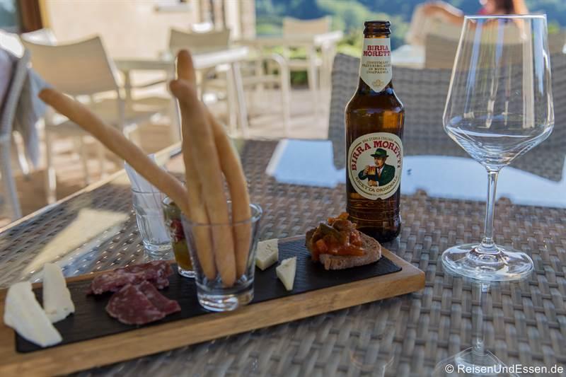 Bier mit Grissini, Salami, Käse und Oliven im Restaurant im Relais Montemario
