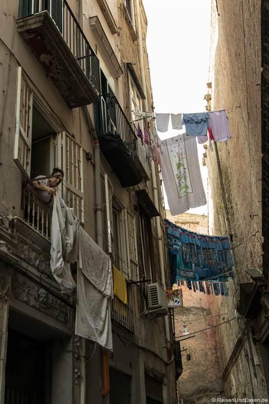 Frau beim Aufhängen von Wäsche im Centro Storico von Neapel