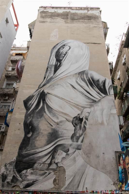 Frau mit Schleier an einer Hauswand