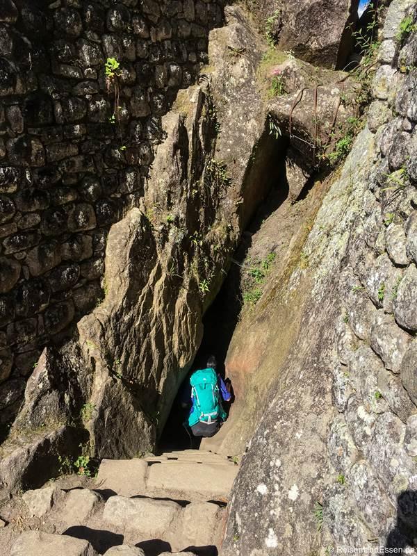 Abstieg durch eine Felsspalte vom Huayna Picchu in Peru
