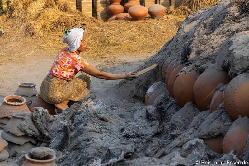Burmesische Frau entfernt Asche von den Terrakotta-Krügen