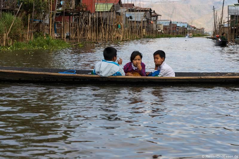 Kinder im Boot bei den Häusern auf Stelzen