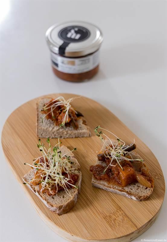 Vorspeise süßsaures Gemüse mit Brot auf einem Holzbrett