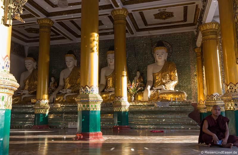 Mönch und Buddhas in der Shwedagon Pagode in Yangon