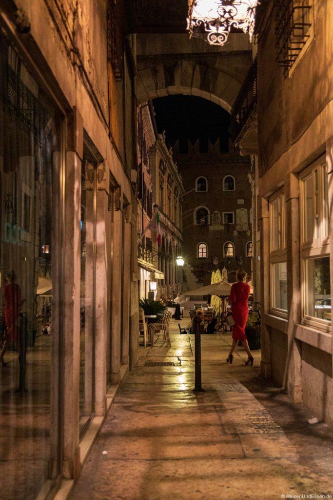 Frau in Rot bei der Piazza dei Signori in Verona