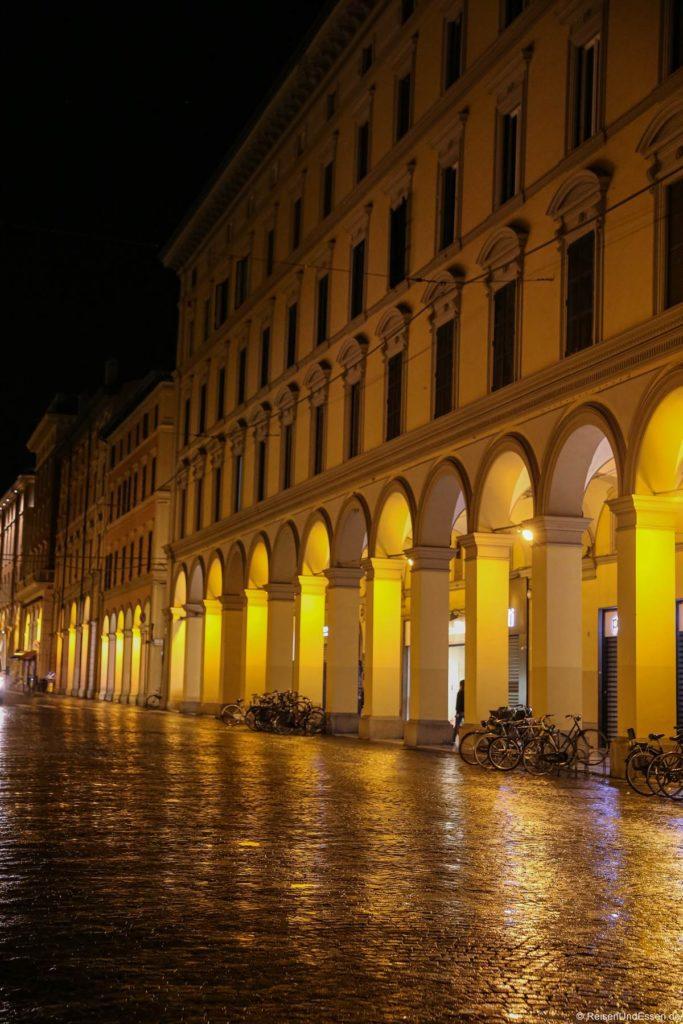 Arkaden mit Pflastersteinen im Regen bei Nacht in Bologna
